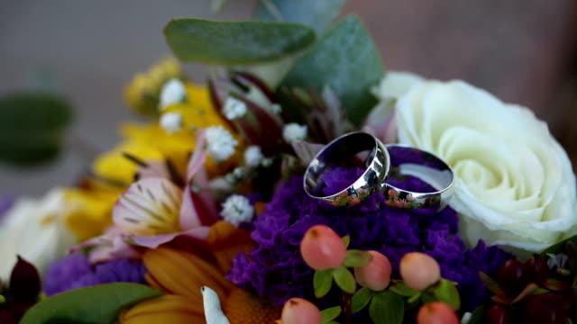 vídeos de stock e filmes b-roll de wedding rings and bouquet - trílio