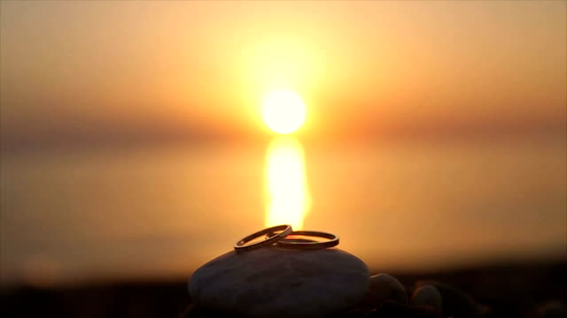 wedding rings on the beach at sunset,romantic and love concept - wife stock videos & royalty-free footage