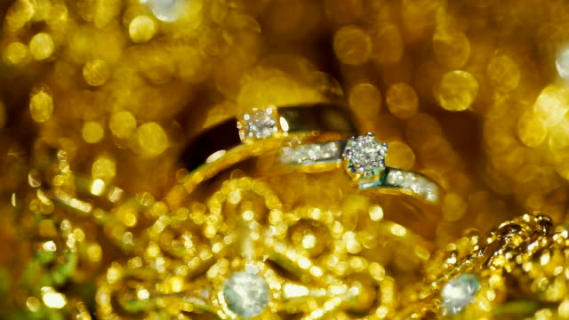 wedding rings with golden textured background. wedding theme. - silver coloured stock videos & royalty-free footage