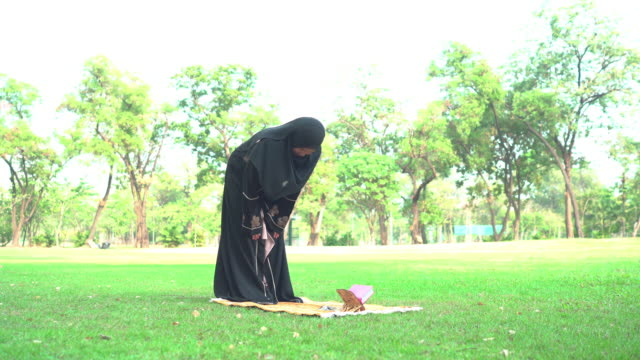 weekend activities of asian muslim pregnant in a public park, side view: a mid woman with a completely religious black dress and covering face, hijab,  having a picnic, praying on prayer mat from standing. - religious dress stock videos & royalty-free footage