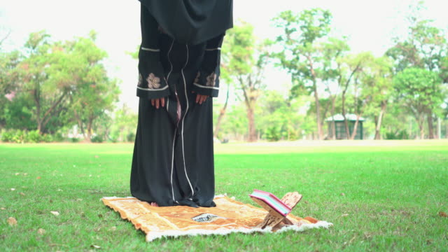 weekend activities of asian muslim pregnant wearing religious clothes called hijab in a public park. side view: a mid woman with a completely religious black dress and covering face having a picnic, praying on prayer mat from standing. - religious dress stock videos & royalty-free footage