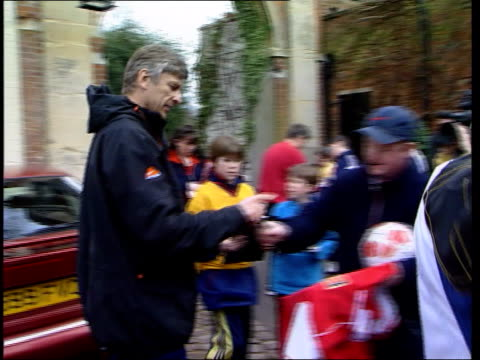 london gir int i/c london ext arsene wenger signing autographs and posing with two young children wenger signing more autographs int arsene wenger... - アーセン・ベンゲル点の映像素材/bロール