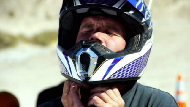 cu weekend warrior taking off his dirt bike helmet / salton city, california, usa - helmet stock videos & royalty-free footage