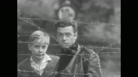 vidéos et rushes de weeping woman begs border guards to let her cross to west berlin - 1961
