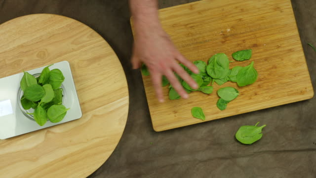 Weighing spinach leaves.