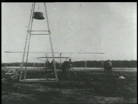 vídeos de stock e filmes b-roll de b/w 1903 weight lowering as wright brothers airplane starts on airfield away from camera - 1903