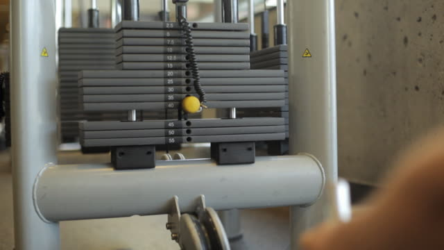 stockvideo's en b-roll-footage met ms tu weights machine pulley pounds plates nautilus in gym / vancouver, british columbia, canada - zwaar