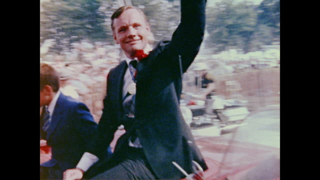 vídeos de stock e filmes b-roll de a welcome home parade for apollo 11 includes returning astronaut neil armstrong who waves to the crowd from the back of a moving car - regresso ao lar