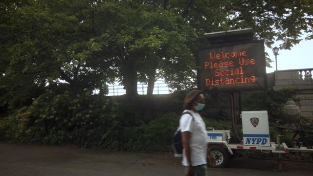 "vidéos et rushes de ""welcome please use social distancing"" sign in central park new york city - central park manhattan"