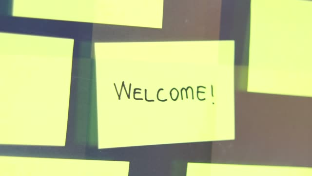 welcome post-it concept. businessman sticks a post-it on the glass of meeting room. - note pad video stock e b–roll