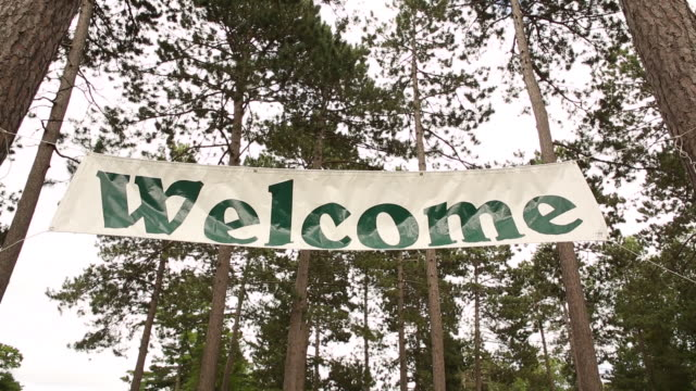 A Welcome sign hung in the trees outdoors.