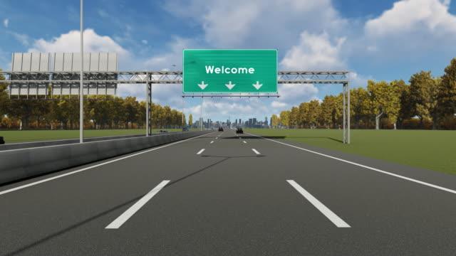 """""""välkommen"""" text på skylten på motorvägen som anger ingången till staden 4k lager video - informationsskylt bildbanksvideor och videomaterial från bakom kulisserna"""