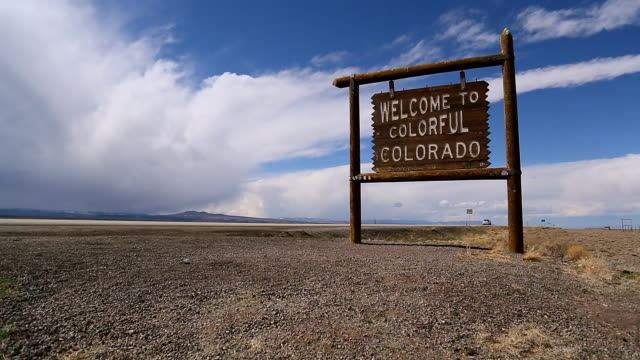 vidéos et rushes de ws pov welcome to colorful colorado sign with mountains in background and car driving past / san antonio, colorado, united states - colorado