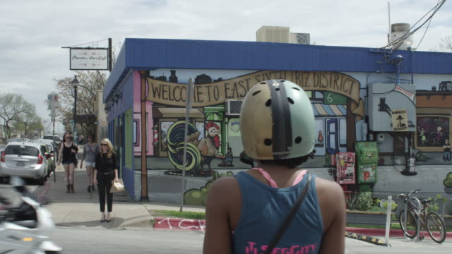 stockvideo's en b-roll-footage met ws of welcome to east sixth ibiz district mural on side of building with segway scooters passing by - austin texas