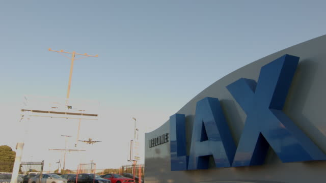 'Welcome to LAX' sign in foreground with jet airliner flying overhead on approach to landing