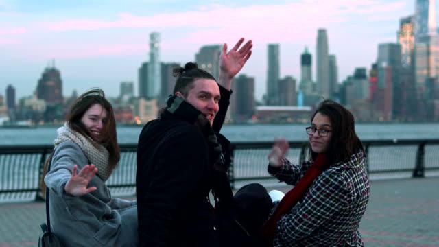 Willkommen in New York! Drei junge Freunde, junger Mann und zwei Teenager Mädchen sitzen und reden an der Waterfront in Hoboken, New Jersey