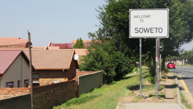 'welcome to soweto' signage. young man walks out of frame. - ソウェト点の映像素材/bロール
