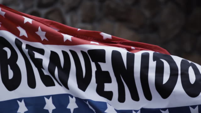 Welcoming Bienvenidos flag waving in the air in a Spanish neighborhood - slow motion.
