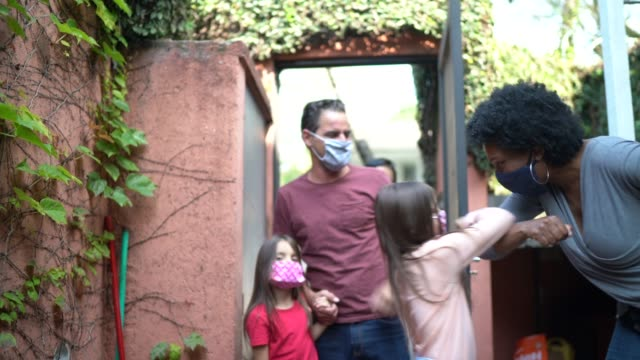 welcoming friends at home during pandemic using face mask and greeting with elbow bump - social gathering stock videos & royalty-free footage