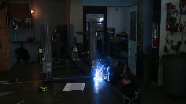 vídeos de stock e filmes b-roll de welder and fabricator uses a mig welder to attach legs to a steel table - trabalho de metal