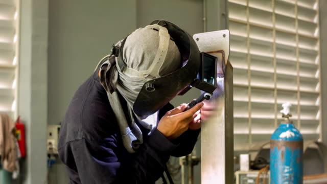 hd dolly ms : schweißer in der produktion-workshop - schutzbrille stock-videos und b-roll-filmmaterial