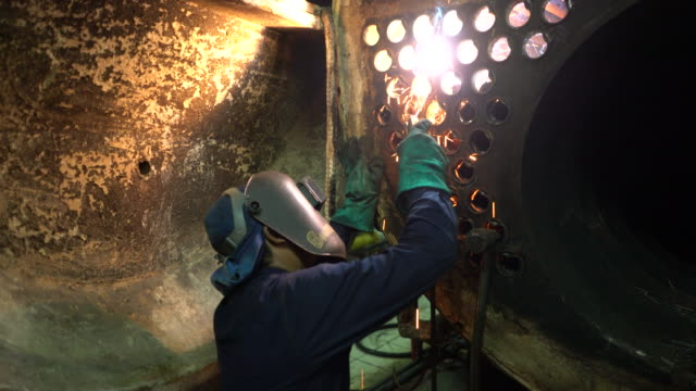 Welder at work in boiler industry.