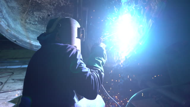 welder at work in boiler industry. - protective mask workwear stock videos and b-roll footage