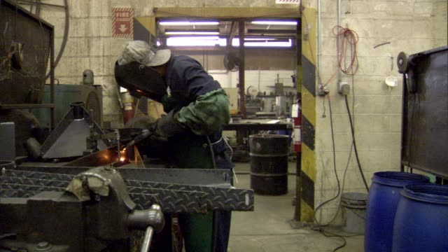 welder bending over welding table soldering metal plates in factory; welder lifts his helmet, releases metal plate from grip and adjusts it to... - welding helmet stock videos & royalty-free footage