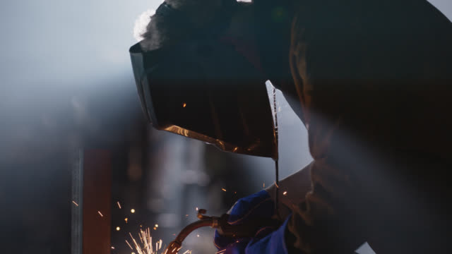 slo mo cu welder bonds metal together, removes protective mask to examine his work, replaces mask to continue working - welding stock videos & royalty-free footage