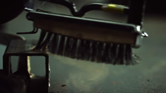 vídeos de stock, filmes e b-roll de um soldador escovas afastado aparas do metal ao soldar em uma oficina - arte e artesanato assunto