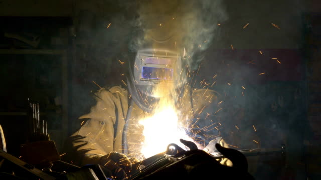 welder creates parts and smoke as he works on machinery. - kunsthandwerker stock-videos und b-roll-filmmaterial