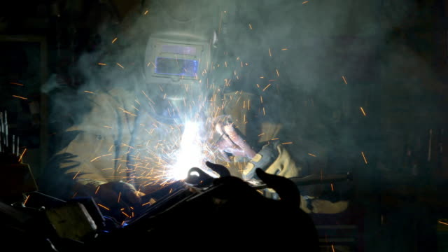 welder creates parts and smoke as he works on machinery. - welding stock videos & royalty-free footage