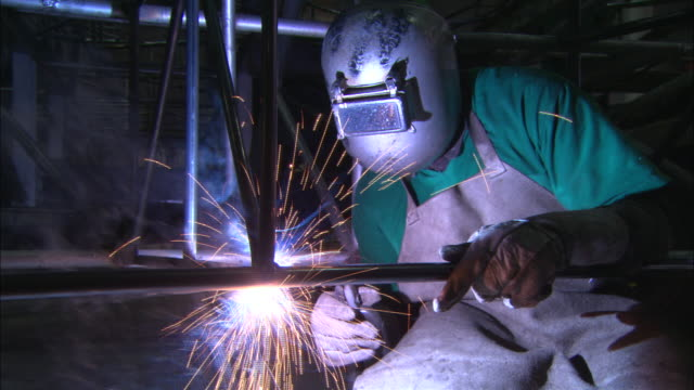 a welder creates sparks as he uses a blowtorch. - welding stock videos & royalty-free footage