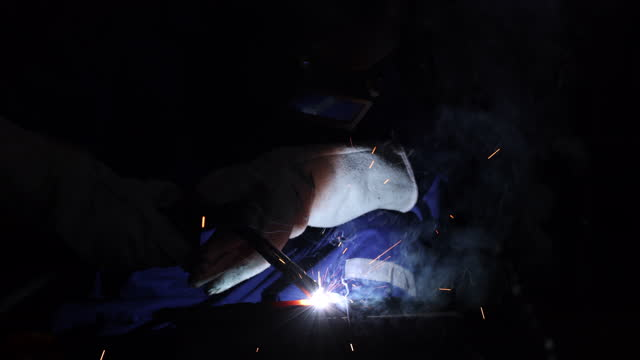 welder in welding helmet welding metal, spark flying - welding helmet stock videos & royalty-free footage