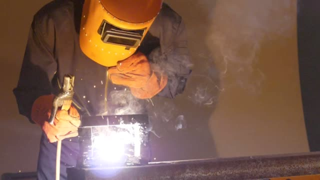 slo mo : welder in workshop - welding helmet stock videos & royalty-free footage