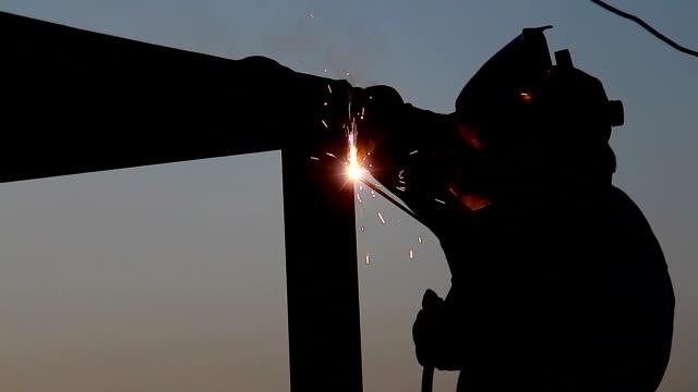 vídeos y material grabado en eventos de stock de soldador está trabajando en la puesta de sol en plataforma petrolera - soldar