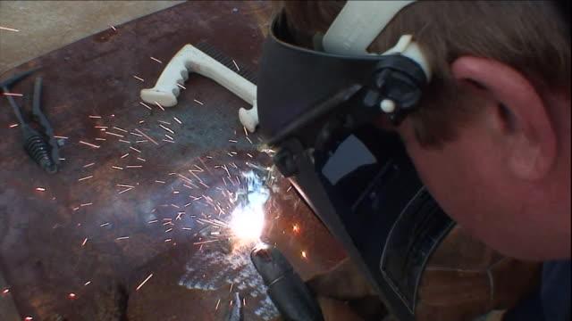 a welder lights his torch and welds sheet metal. - welding helmet stock videos & royalty-free footage