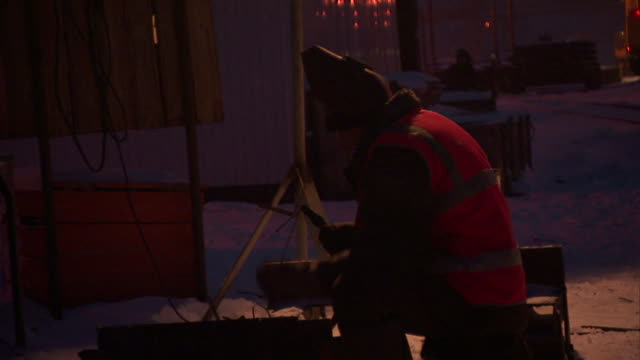 a welder lowers his face shield before welding at a construction site in the snow. - welding helmet stock videos & royalty-free footage