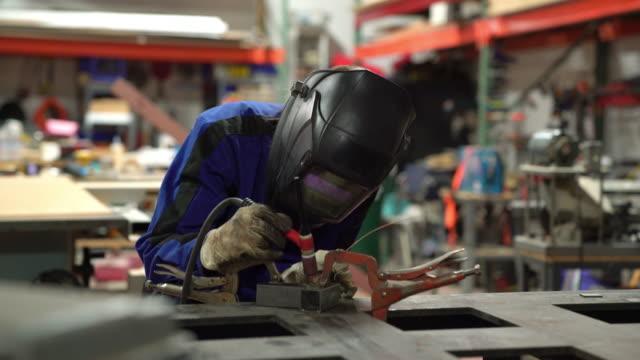 tig welder preparing to work in her workshop - welding torch stock videos & royalty-free footage