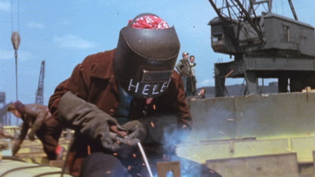 Welder sitting on a pipe welding a bracket on the pipe and lifting mask to look at her work / Newport News Virginia United States