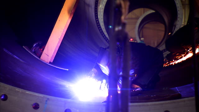 a welder uses an arc welder to weld a seam in a confined area. - welding helmet stock videos & royalty-free footage