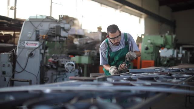 stockvideo's en b-roll-footage met lasmachine met een haakse slijper op metalen plaat - productielijn werker