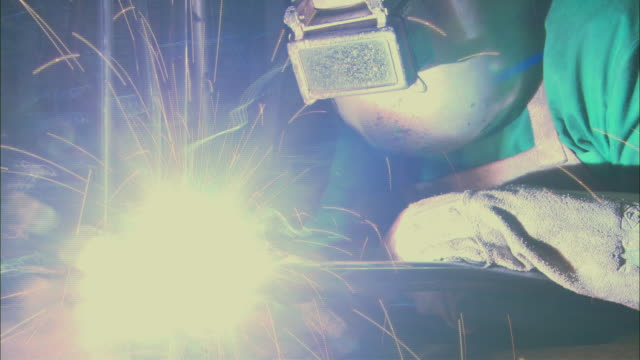 MS PAN Welder wearing protective gear uses a small blowtorch while working on metal rod/ Brazil