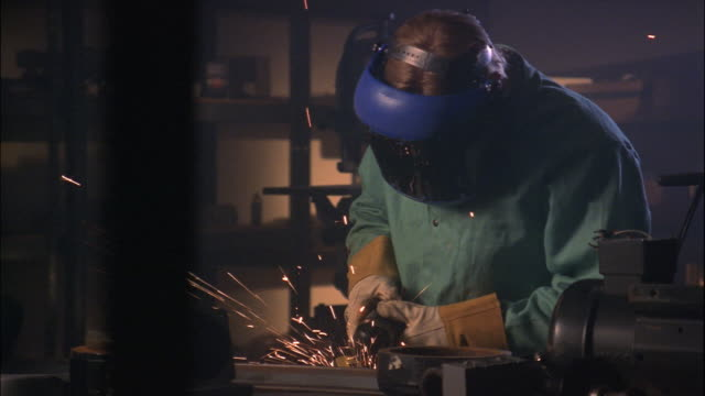 A welder wears a protective mask as he grinds metal in his workshop.