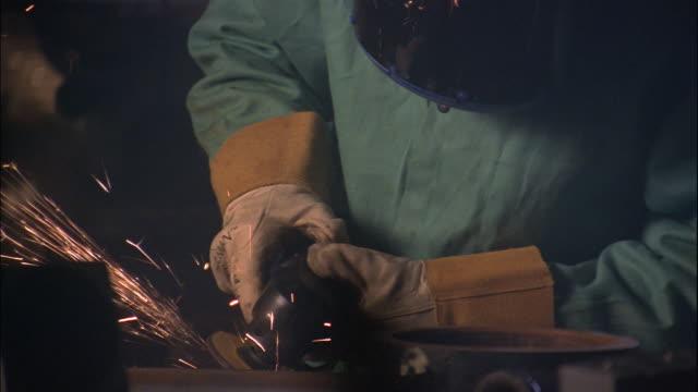 A welder wears a protective mask while grinding metal in his workshop.