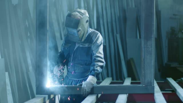 slo mo ds welder welding a metal frame - schweißen stock-videos und b-roll-filmmaterial