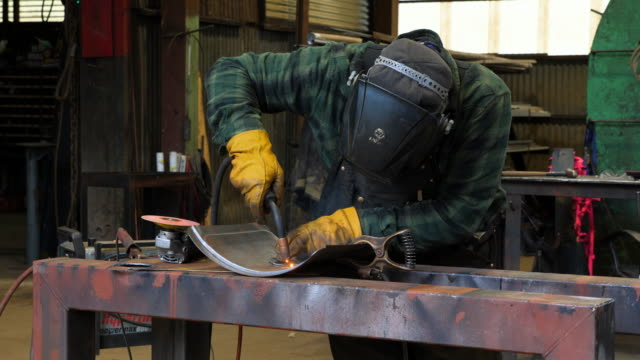 MS Welder welding patch on sheet of metal in metal shop