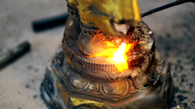 Welder welding steel sculpture and repair detail of the Buddha while sparks and smoke.