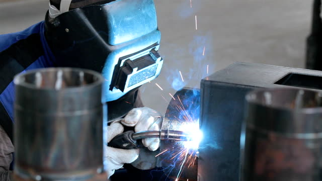 welder welds metal parts on a production line. - welding stock videos & royalty-free footage