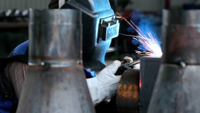 schweißer schweißt metallteile auf einer produktionslinie. - schweißen stock-videos und b-roll-filmmaterial
